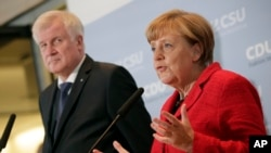 FILE - German Chancellor Angela Merkel, right, and the Governor of the German State of Bavaria, Horst Seehofer, left, address the media during a statement about their talks on the migrant influx in Berlin, Germany, Nov. 3, 2015.