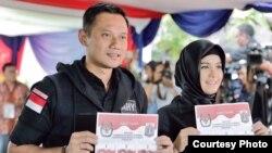 Calon gubernur Jakarta Agus Harimurti Yudhoyono bersama istri memberikan suara di sebuah TPS (15/2). (Courtesy: Anung Anindito)