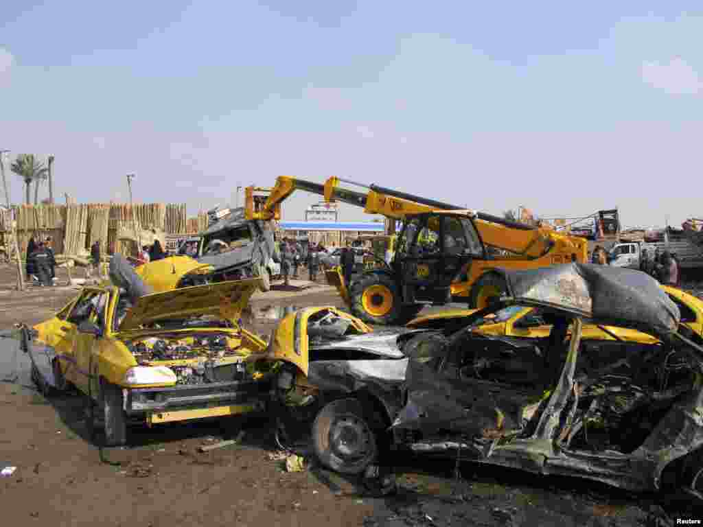 Security personnel and residents gather at the site of a car bomb attack in Kadhimiya, Iraq, Feb. 8, 2013.