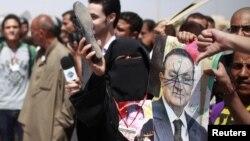 Una mujer sostiene un zapato y un manchado retrato del ex presidente egipcio Hosni Mubarak, que fue condenado este sábado 2 de junio a cadena perpetua.