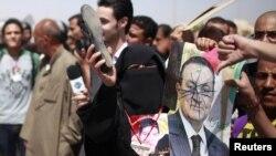 Seorang perempuan Mesir membawa poster Mubarak dan mengacungkan sepatu dalam unjuk rasa di luar pengadilan Kairo (2/6). Banyk warga Mesir kecewa atas vonis terhadap Mubarak.