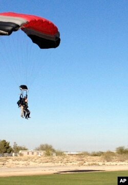 Former U.S. Rep. Gabrielle Giffords (r) comes in for a landing during a tandem skydive, Jan. 8, 2014, in Tucson, Arizona.