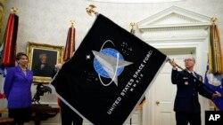 在白宫椭圆形办公室,空军部长芭芭拉·巴雷特(左)注释着总军士长罗杰·陶伯曼展示美国太空军的军旗。(2020年5月15日)