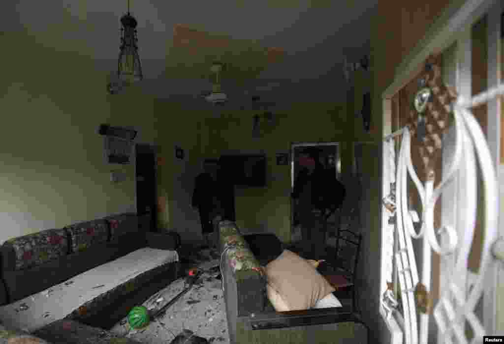 Men inspect their home, which was damaged after a car bomb attack in Baghdad, Feb. 3, 2014.