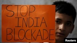FILE - A student holding a placard takes part in a protest to show solidarity against the border blockade in Kathmandu, Nepal, Nov. 27, 2015.
