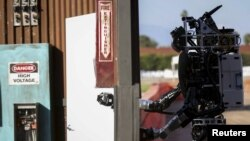 FILE - An earlier version of Boston Dynamics' Atlas robot opens a door during the Defense Advanced Research Projects Agency (DARPA) Robotic Challenge in Pomona, California, June 6, 2015.