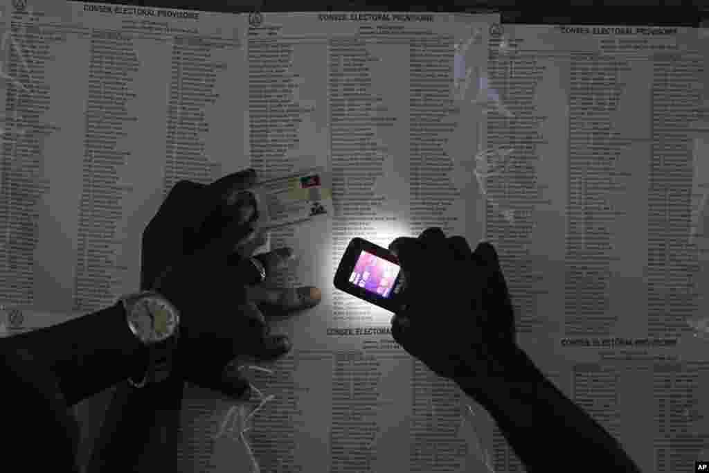 A voter uses his cell phone flashlight to find his name on a voters list during elections in the Petion-Ville suburb of Port-au-Prince, Haiti.