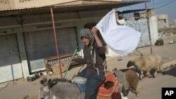 5일 이라크 모술의 이라크 정부군과 ISIL의 교전 지대에서 탈출한 한 남성이 백기를 흔들며 지나가고 있다.
