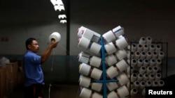 Pekerja memeriksa kualitas benang di pabrik di Bandung.