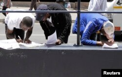 FILE - Zimbabweans fill out application forms outside immigration offices in Johannesburg, South Africa, Dec. 31, 2010.