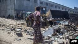 Une femme regarde un bulldozer qui enlève les décombres de sa maison démolie à Xwlacodji, dans le 5ème arrondissement de Cotonou, le 3 septembre 2019, après le passage des bulldozers.