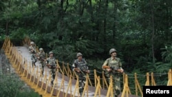Pasukan Keamanan Perbatasan India (BSF) berpatroli di atas jembatan yang dibangun dekat garis kontrol (LoC), di wilayah Sabjiyan, distrik Poonch, 8 Agustus 2013. Garis LoC merupakan sebuah garis gencatan senjata yang memisahkan wilayah Kashmir yang disengketakan India dan Pakistan (Foto: dok).