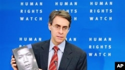 Human Rights Watch executive director Kenneth Roth shows the group's annual review during a media conference. Human Rights Watch report the silence and complicity of the U.S., U.N., EU and major European nations in dealing with rights-abusing developing