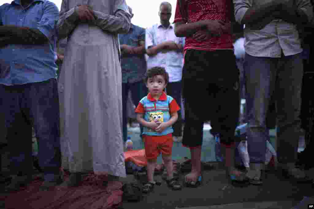 An Egyptian child attends prayers with his father at a protest near Cairo University in Giza, Egypt, August 1, 2013.