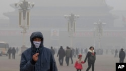 FILE - A man wears a mask on Tiananmen Square in thick haze in Beijing.