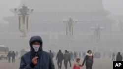Seorang pria menggunakan masker di tengah asap tebal di Alun-Alun Tiananmen, Beijing (29/1). (AP/Ng Han Guan)