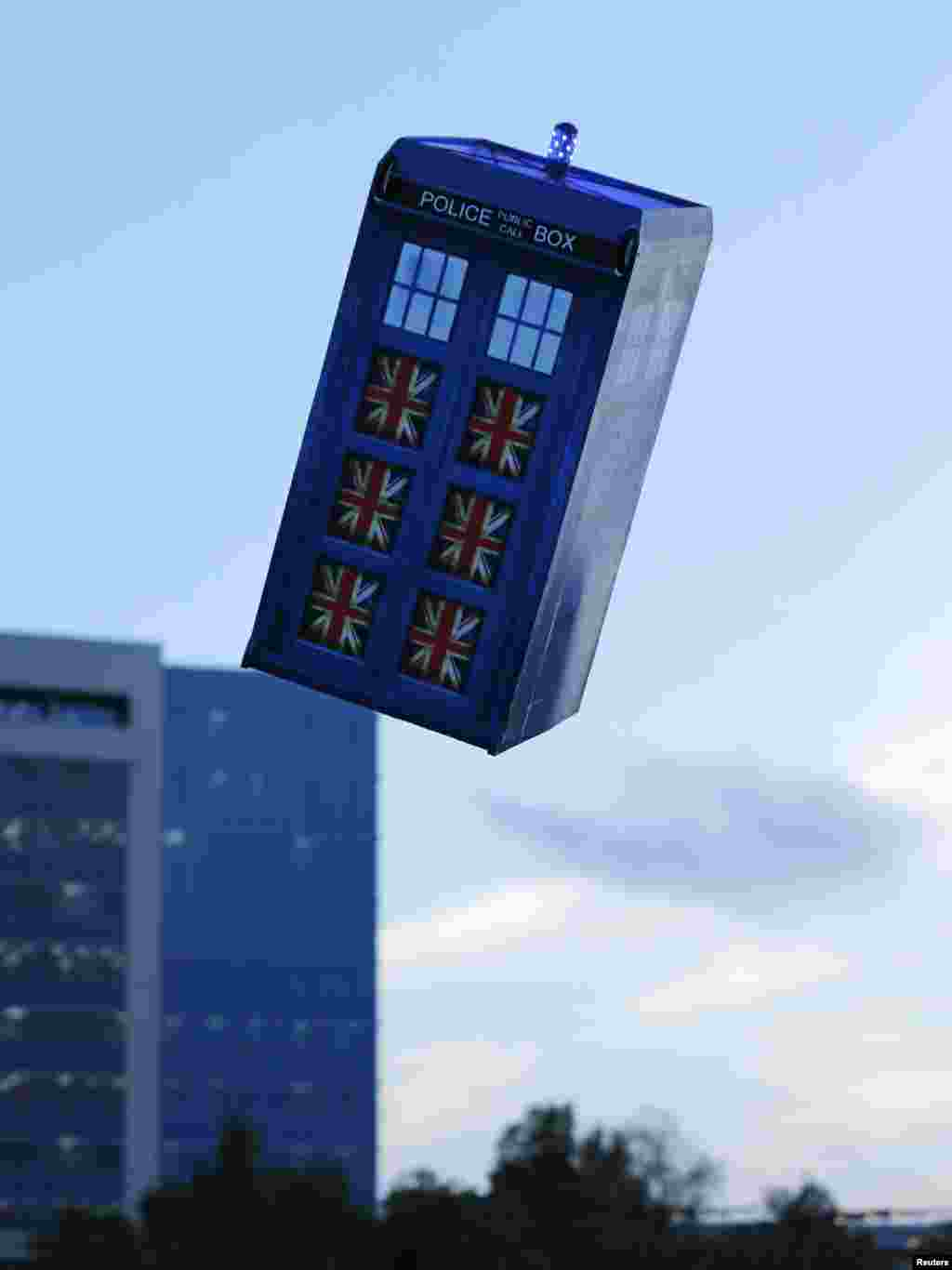 """A flying """"Tardis"""" remote control air craft is test-flown past a building in San Diego, California, Nov. 18, 2013. Inventor Otto Dieffenbach built the """"Tardis"""", an old-fashioned police call box used as a time machine in the British television series Dr. Who, to celebrate the show's 50th season this year."""