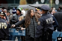 A New York Police Department officer searches a woman as she enters the Times Square, Dec. 31, 2015. Around 1 million people are expected to converge on Times Square for the annual New Year's Eve celebration.
