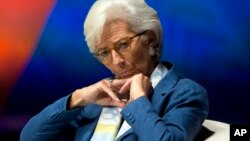 La directora del Fondo Monetario Internacional, Christine Large, escucha al presidente del Banco Mundial, Jim Yong Kim, en Lima, Perú.