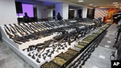 Soldiers stand guard during a presentation of weapons seized during an operation against the Gulf cartel in Mexico City, (File).
