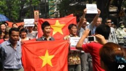 Protesters shout their slogan to protest against China while marching in Hanoi, Vietnam, Sunday, July 17, 2011.