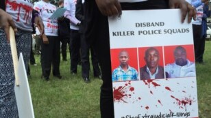 FILE - A protester holds a sign picturing human rights attorney Willie Kimani, his client Josephat Mwenda and their taxi driver Joseph Muiruri allegedly killed by police, at a rally in Nairobi, Kenya, July 4, 2016. (J. Craig/VOA)
