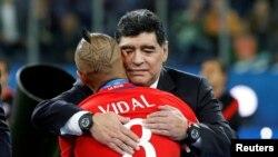 Diego Maradona memeluk pemain Chile, Arturo Vidal, setelah pertandingan Chile melawan Jerman di Stadion St. Petersburg di Rusia, 2 Juli 2017. (Foto:Dok)