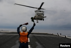 Akiko Ihara, a female flight deck crew of Japanese helicopter carrier Kaga, guides for the landing of a SH-60K Sea Hawk helicopter on the flight deck in the Indian Ocean, Indonesia, Sept. 24, 2018.