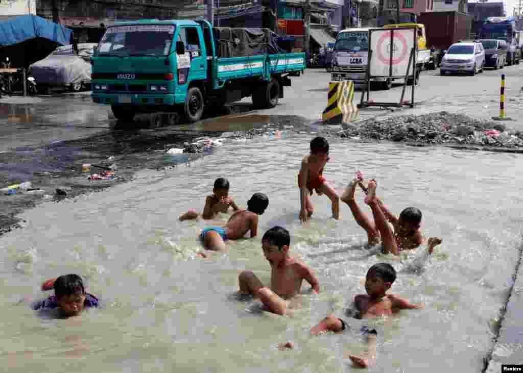 شنا کردن پسر بچه ها در آب جمع شده در جادههای در دست تعمیر در مانیل، فیلیپین
