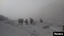 Japan Self-Defense Force (JSDF) soldiers conduct rescue operations near the peak of Mount Ontake, which erupted September 27, 2014 and straddles Nagano and Gifu prefectures, central Japan, in this handout photograph released by the Joint Staff of the Defe