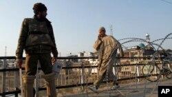 Seorang warga sipil Kashmir berjalan melewati seorang polisi India yang berjaga di dekat pagar berduri saat diberlakukannya jam malam di wilayah Srinagar, India, 9 February 2013. (AP Photo/Mukhtar Khan). Seorang warga Kashmir yang divonis bersalah atas perannya dalam serangan terhadap parlemen India tahun 2001, Afzal Guru, telah dihukum gantung di sebuah penjara India, Sabtu (9/2).