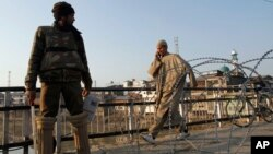 A Kashmiri civilian walks past an Indian policeman standing near a barbed wire during curfew in Srinagar, India, February 9, 2013.