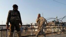Civil prolazi pored policajca kraj bodljikave žice tokom policijskog časa u Srinagaru, Indija