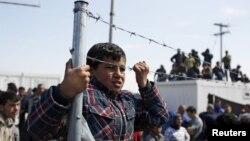 29일 그리스-마케도니아 국경 지역에서 시리아 난민들이 경찰과 충돌한 가운데, 난민들이 이를 지켜보고 있다.