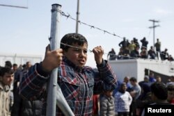 Migrants and refugees look on after minor clashes with Greek policemen occurred at a makeshift camp at the Greek-Macedonian border near the village of Idomeni, Greece, March 29, 2016.
