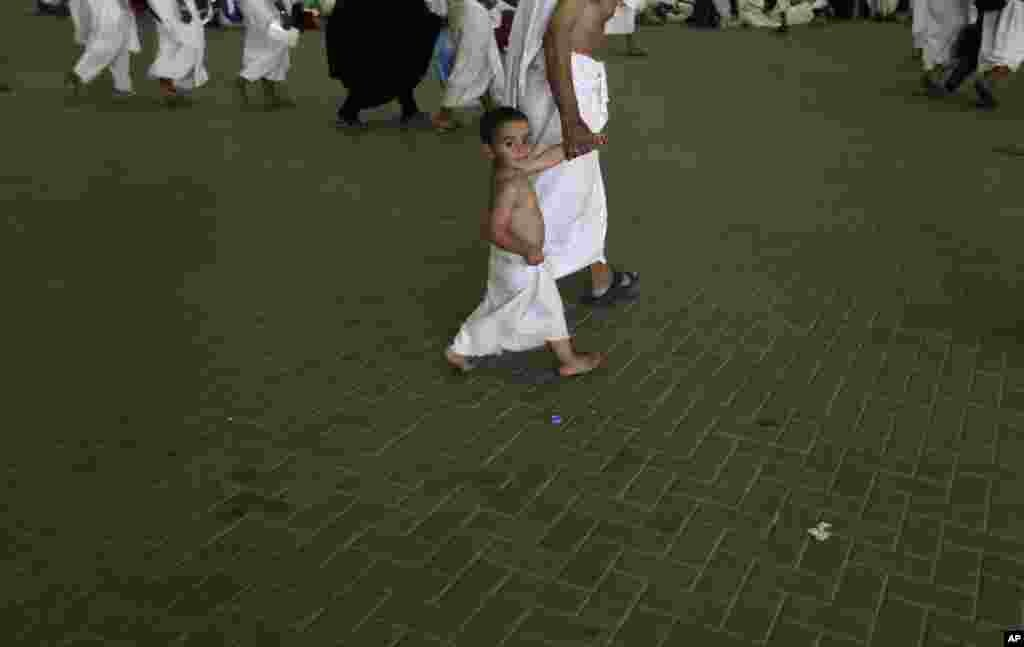 Youssef, 3, a Muslim pilgrim from Egypt walks with his grandfather to casts stones at a pillar near the Saudi holy city of Mecca, Saudi Arabia, October 26, 2012.