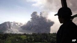 Seorang pria memandangi erupsi Gunung Sinabung dari Tiga Pancur, Sumatera Utara, Rabu (24/6).