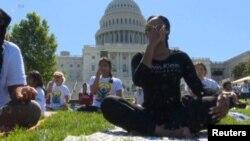 Ratusan praktisi melakukan Yoga di lapangan gedung Capitol Washington DC hari Sabtu (16/6).