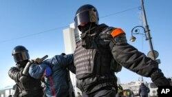 Polis əməkdaşları Vladivostokda müxalifət lideri Aleksey Navalnının həbs olunmasına etiraz olaraq keçirilən aksiya iştirakçısını saxlayır, 31 yanvar, 2021.