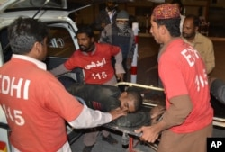 FILE - Pakistani volunteers rush an injured person to a hospital in Quetta, Pakistan, Oct. 24, 2016, after two separate attacks in Pakistan. Gunmen stormed a police training center in the southwestern province of Baluchistan Monday, leaving several people woun