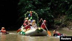 Novanto Rahman dan pasangannya, Sandra Fidelia Novianti, yang bekerja sukarela dalam inisiatif pembersihan Ciliwung, melangsungkan upacara pernikahan mereka di sungai itu (18/12). (Reuters/Adi Kurniawan)