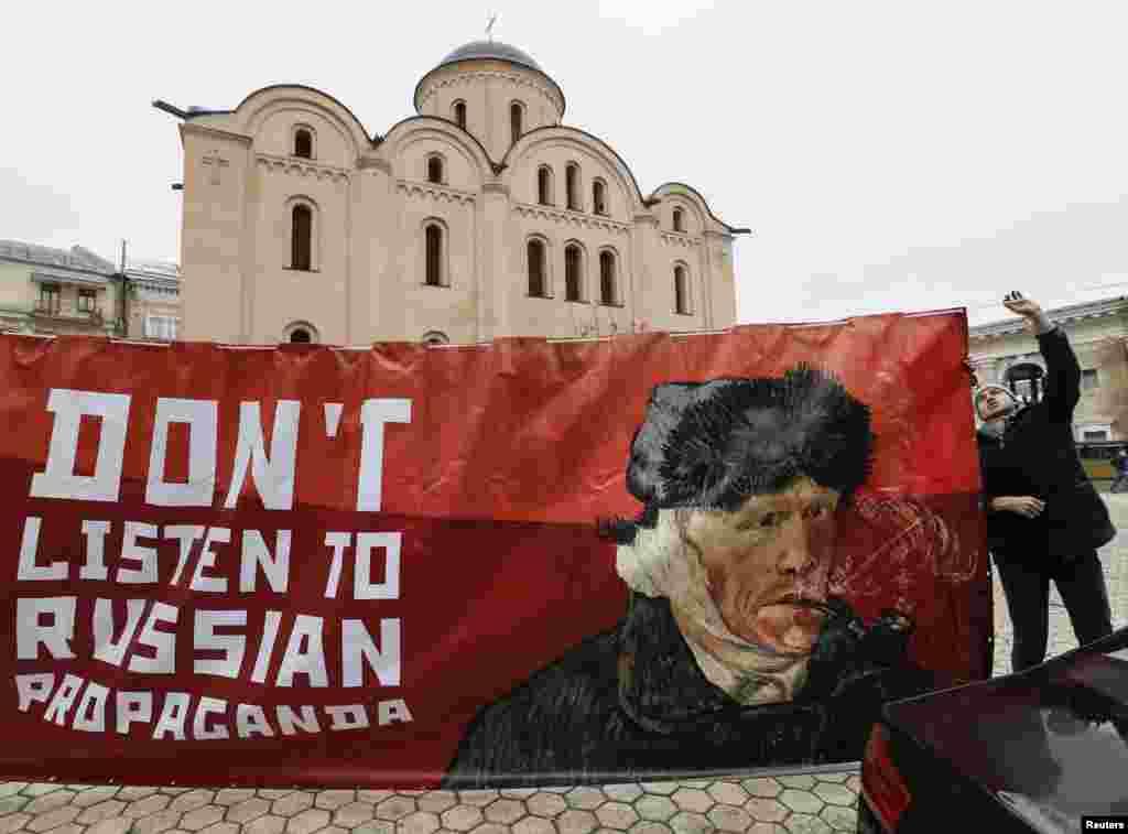Một nhà hoạt động giăng biểu ngữ với bức chân dung họa sĩ người Hà Lan Vincent van Gogh bên ngoài Đại sứ quán Hà Lan tại Kiev, Ukraine. Những nhà hoạt động kêu gọi người Hà Lan phớt lờ điều mà họ nói là tuyên truyền, trước Hiệp định Liên kết Ukraine-EU sắp tới.