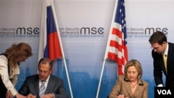 Menteri Luar Negeri AS Hillary Clinton (kanan) dan Menlu Rusia Sergei Lavrov menandatangani pertukaran dokumen resmi START di sela-sela Konferensi Keamanan di Munich, Jerman.