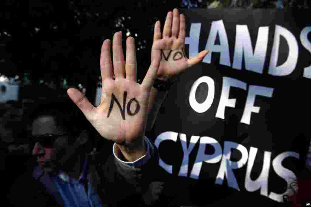 Protesters hold up their hands as they protest outside the parliament in capital Nicosia, Cyprus, March 18, 2013.