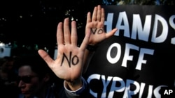 抗议者2013年3月18日在塞浦路斯尼科西亚议会外面举起他们的双手