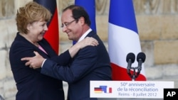 German Chancellor Angela Merkel, and French President Francois Hollande react after a speech in front of the Reims cathedral in Reims, eastern France, July 8, 2012.
