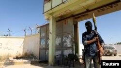 Dân quân đứng gác trước 1 doanh trại sau vụ giao tranh ở Benghazi, 16/5/2014.