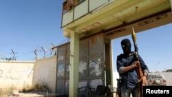 ນັກລົບຄົນນຶ່ງ ຂອງກຸ່ມອິສລາມຫົວຮຸນແຮງ ຢືນຍາມທາງເຂົ້າ ຄ້າຍກຸມພາ 17 ຫລັງຈາກໄດ້ເກີດການປະທະກັນ ທີ່ເມືອງ Benghazi (16 ພຶດສະພາ 2014)