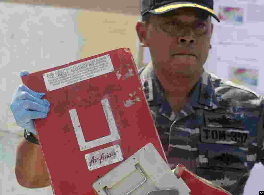 Commander of Indonesian Navy ship KRI Bung Tomo Col. Yayan Sofyan holds a piece of the AirAsia Flight 8501 recovered in search operations for the ill-fated jetliner, during a press conference at the Navy's Eastern Fleet Naval Base in Surabaya, East Java, Indonesia, Jan. 5, 2015.
