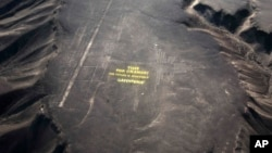 "Greenpeace activists stand next to massive letters delivering the message ""Time for Change: The Future is Renewable,"" next to the hummingbird geoglyph in Nazca in Peru. (File)"